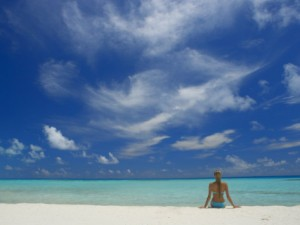 papadopoulos-sakis-woman-sitting-on-the-beach-looking-out-to-sea-maldives-indian-ocean
